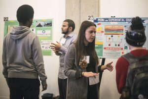 Students listening to poster presenters